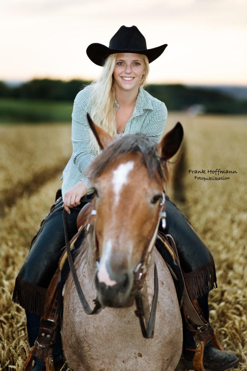 Cowgirl auf dem Pferd im Abendlicht.