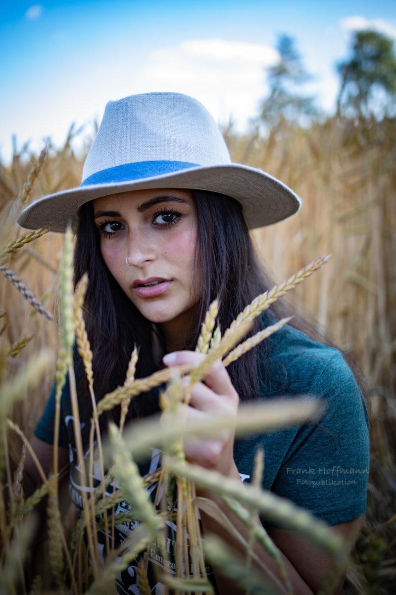 Das Bild dien der Visualisierung einer schönen jungen Frau mit Hut im Kornfeld.