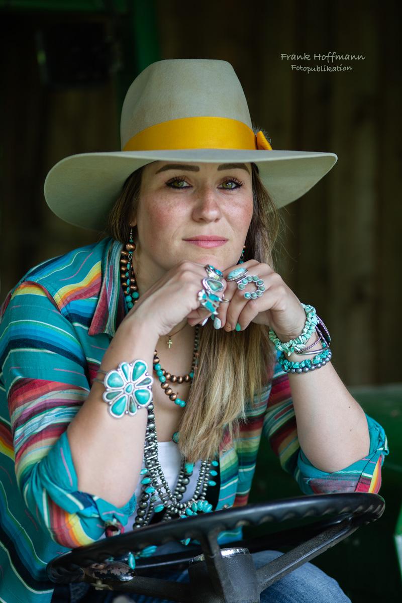 Traumschönes Portrait von Cowgirl Sandra Baumann auf ihrem Traktor.