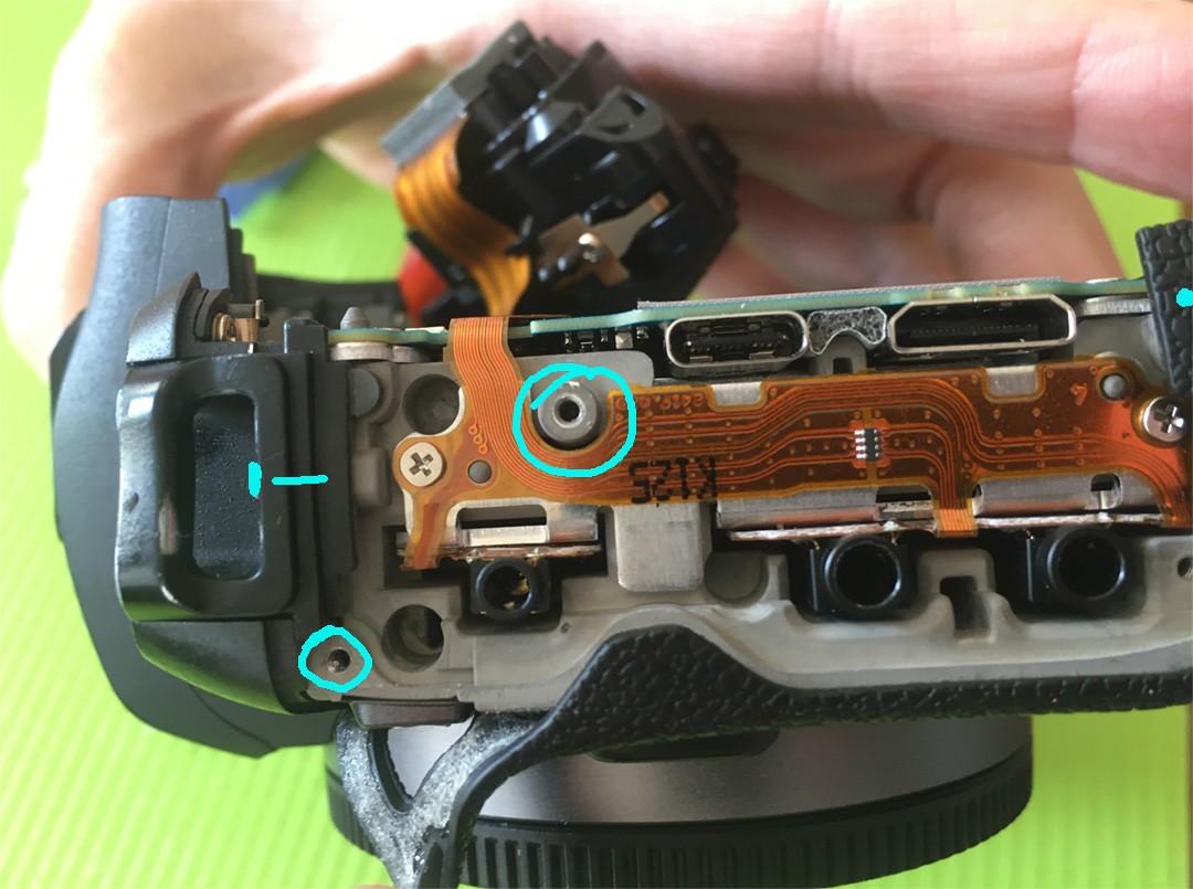 Linke Kameraseite hiinter der Kunstoffabdeckung befindet sich noch eine silberne Schraube die zu entfernen ist.